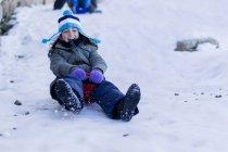 Fille sur un traîneau glissant sur une colline dans la neige — Photo de stock