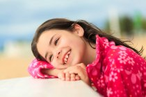 Smiling girl leaning on the edge of a table at the beach — Stock Photo