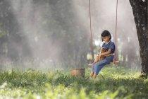 Menina sentada em um balanço com o cão no colo — Fotografia de Stock
