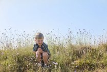 Улыбающийся мальчик сидит в зеленом поле и смотрит на цветы — стоковое фото