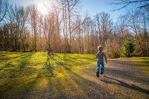 Rear view of a Boy running on path in countryside — Stock Photo