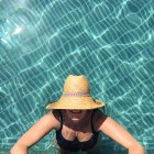Woman wearing straw hat standing in swimming pool and looking up — Stock Photo