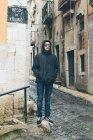 Мальчик-подросток в куртке с капюшоном и солнцезащитных очках стоит на улице, Альфама, Лисбон, Португалия — стоковое фото