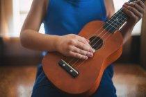 Abgeschnittenes Bild eines Mädchens, das eine Ukulele spielt — Stockfoto