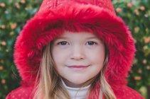 Portrait d'une jeune fille porte un manteau rouge en regardant la caméra — Photo de stock