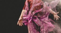 Sección media de una chica en una falda de tul jugando en el polvo contra el fondo negro - foto de stock