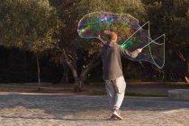 Mann im Park stehen und machen große Seifenblase — Stockfoto