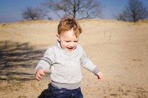 Joyeux petit garçon jouant à l'extérieur — Photo de stock