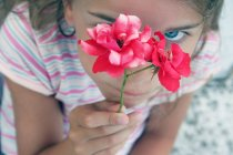 Close-up of Girl holding wild roses and looking at camera — Stock Photo