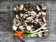 Dish with raw sliced mushrooms, carrots and spring onions on wood — Stock Photo