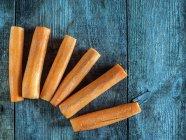 Вид зверху морква кийками на дерев'яний стіл — стокове фото