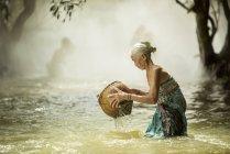 Vista laterale della donna anziana pesca in corrente in Thailandia — Foto stock