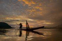 Силует людини на риболовлю на традиційні човна, озеро Bangpra, Таїланд — стокове фото
