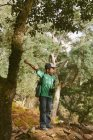 Boy wearing cap standing and cheering in forest — Stock Photo