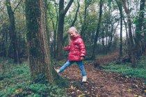 Fille gilet rose pousser l'arbre dans la forêt — Photo de stock