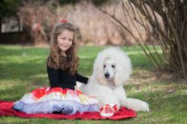 Portrait of girl sitting with white poodle on picnic blanket — Stock Photo