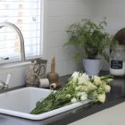 Bunch of beautiful white flowers in kitchen sink — Stock Photo