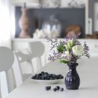 Fresh cut flowers in vase with fresh blueberries on dining table — Stock Photo