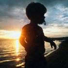 Silhouetted niño jugando en la playa al amanecer - foto de stock