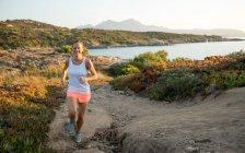 Francia, Córcega, sendero de mujer sonriente corriendo por la costa - foto de stock
