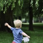 Rear view of little blond boy running in park — Stock Photo