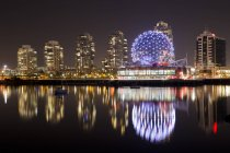 Canada, British Columbia, Vancouver, False Creek, Illuminated skyscrapers reflecting in river — Stock Photo