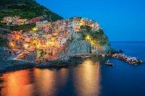Town at dusk with electric lights, Italy, Liguria, Manarola — Stock Photo