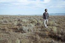 Man wearing sunglasses standing in sagebrush field — Stock Photo