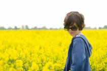 Jovem rapaz de óculos permanente contra o campo de flores amarelas — Fotografia de Stock