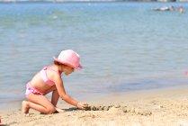 Menina usando chapéu rosa e maiô jogando na praia de areia — Fotografia de Stock