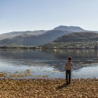UK, Scotland, Boy throwing stones in water with mountains on background — Stock Photo