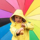 Cute little boy in yellow raincoat with colorful umbrella looking at camera — Stock Photo