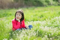 Girl sitting in a field and resting her chin in her hand — Stock Photo