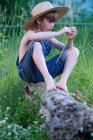 Young boy wearing blue overalls and hat sitting on fallen tree — Stock Photo