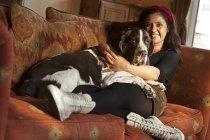 Женщина cuddling старая собака дома на диване — стоковое фото