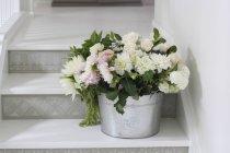 Ведро красивых нежных срезанных цветов на ступеньках — стоковое фото