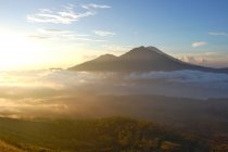 Peak of volcano above clouds at sunrise, Indonesia, Bali — Stock Photo