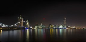 Illuminated London Bridge and Shard building by night and River Thames in foreground, London, USA — Stock Photo