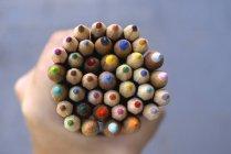 Vista de cerca de la mano humana sosteniendo lápices de colores - foto de stock