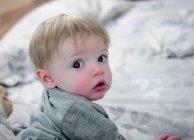 Blond mignon bébé garçon rampant sur lit — Photo de stock