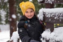 Jeune fille souriante portant debout chapeau jaune en hiver — Photo de stock