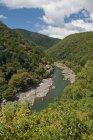 Japan, Kyoto, Arishiyama, Elevated view of river between green hills — Stock Photo