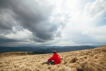 Young man sitting in field with stormy sky on background — Stock Photo