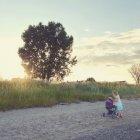 Маленькая девочка с прогулочной коляски, стоящий на пути в природе — стоковое фото