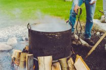 Cropped image of man cooking fish boil at park — Stock Photo