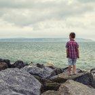 Мальчик стоит на скалах и смотрит на море — стоковое фото