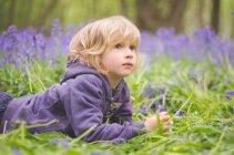 Portrait of thoughtful little boy lying among bluebells — Stock Photo