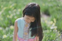 Girl looking down while standing in green meadow — Stock Photo
