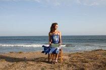 Женщина сидит на стуле на пляже с пишущей машинкой — стоковое фото