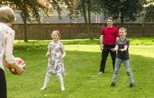 Caucasian family playing with ball at backyard — Stock Photo
